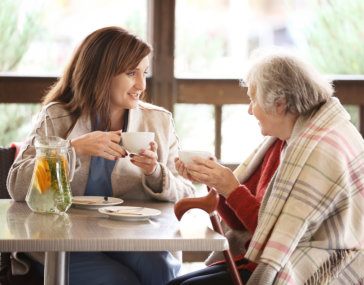 caregiver talking to old woman while sitting