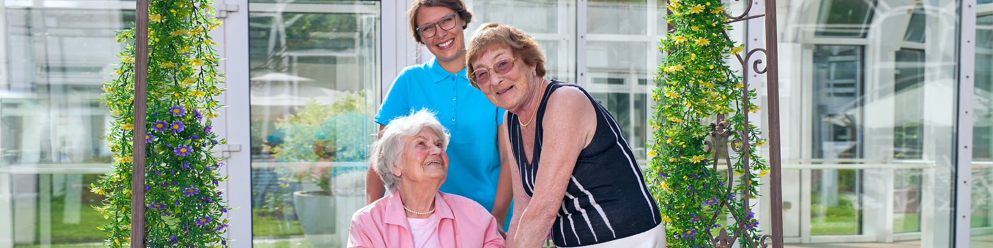 two seniors and caregiver smiling