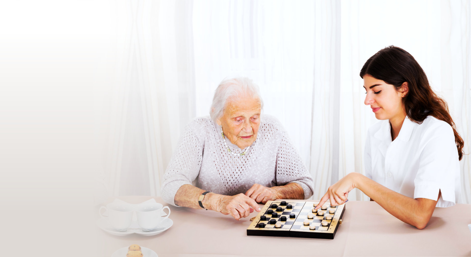 old woman and caregiver playing chess